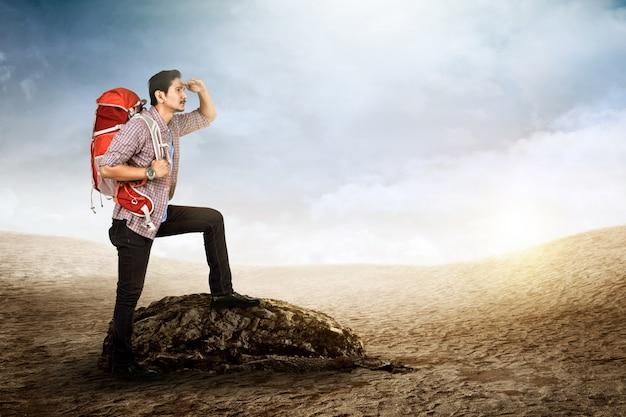 Jovem viajante asiático com mochila, olhando a vista de sua posição