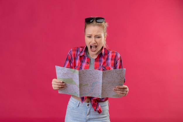 Jovem viajante assustada vestindo camisa vermelha e óculos na cabeça, olhando para o mapa na parede rosa isolada
