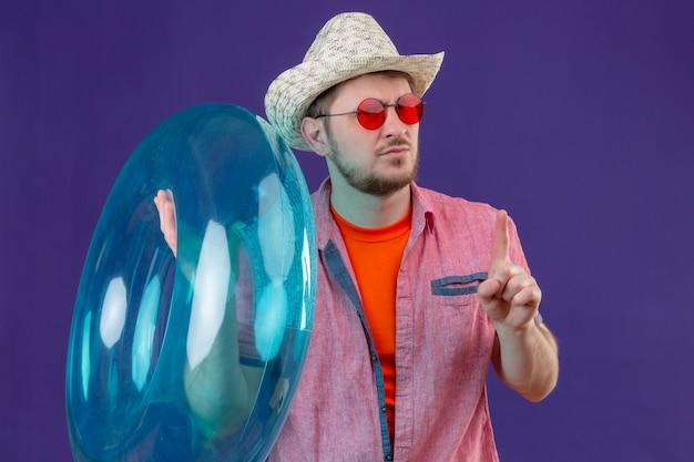 Jovem viajante bonito com chapéu de verão e anel inflável apontando o dedo para cima