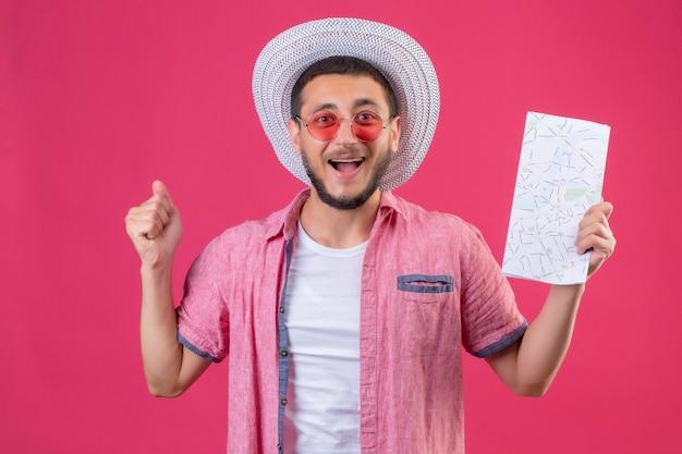 Jovem viajante bonito com chapéu de verão usando óculos escuros segurando o mapa levantando o punho após uma vitória, sorrindo com o conceito de vencedor do rosto feliz em pé sobre o fundo rosa