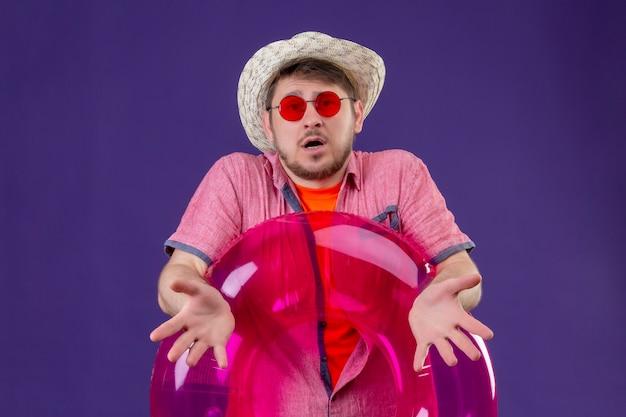 Jovem viajante bonito usando óculos escuros e chapéu de verão segurando um anel inflável e dando de ombros
