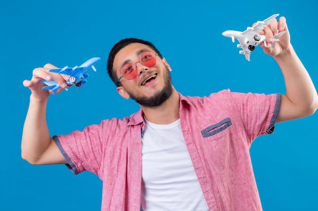 Jovem viajante bonito usando óculos escuros segurando aviões de brinquedo brincando com eles, parecendo feliz e positivo, sorrindo alegremente em pé sobre um fundo azul
