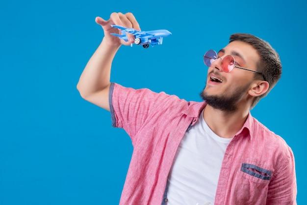 Jovem viajante bonito usando óculos escuros segurando um avião de brinquedo brincando com a bainha, parecendo feliz e positivo, sorrindo alegremente em pé sobre um fundo azul