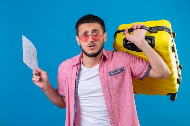 Jovem viajante bonito usando óculos escuros segurando um mapa e uma mala de viagem, parecendo confuso e desapontado em pé sobre um fundo azul