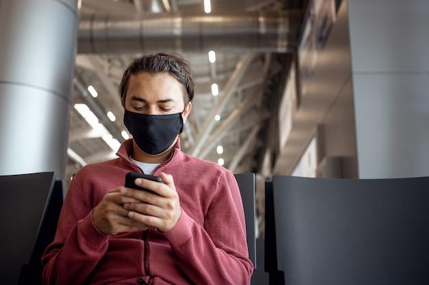 Jovem viajante bonito usando uma máscara no saguão do terminal do aeroporto usando aplicativo de smartphone em área wi-fi pública, mensagens