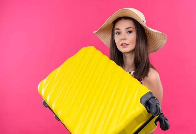 Jovem viajante caucasiana olhando para a câmera com um chapéu segurando uma mala no fundo rosa isolado