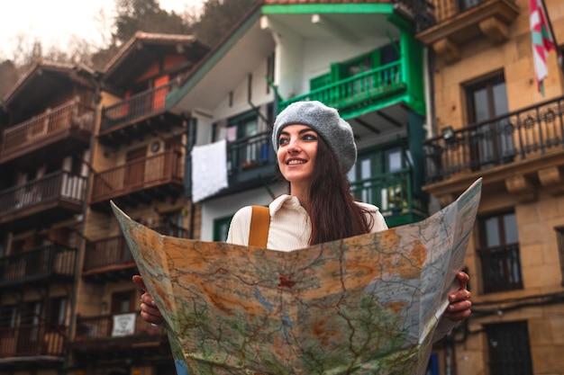 Jovem viajante caucasiana olhando um mapa e fachadas coloridas atrás