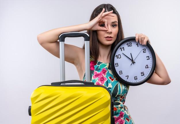Jovem viajante caucasiana segurando um relógio fazendo uma placa de ok e olhando através desta placa, de pé sobre um fundo branco