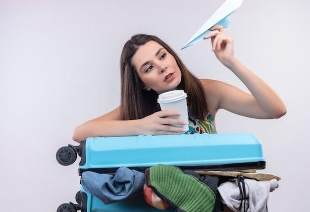 Jovem viajante caucasiana segurando uma xícara de café de plástico e um avião de papel em um fundo branco isolado.