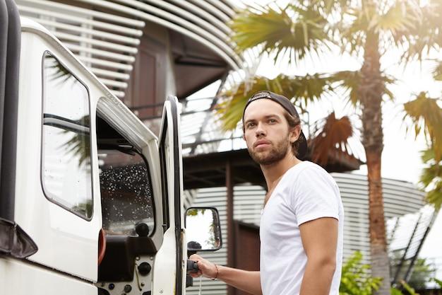 Jovem viajante caucasiano em snapback, ficando em seu veículo off-road branco, pronto para dirigir a corrida de safari