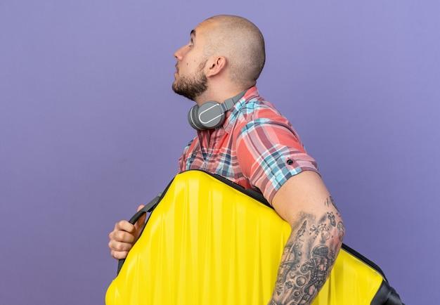 Jovem viajante caucasiano surpreso com fones de ouvido no pescoço, de pé de lado, segurando uma mala isolada no fundo roxo com espaço de cópia