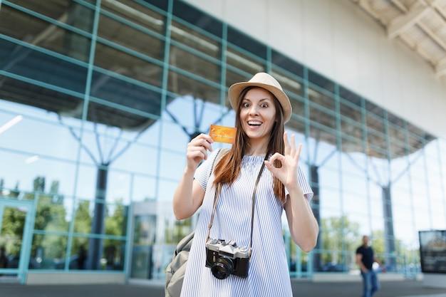 Jovem viajante chocada com uma câmera fotográfica vintage retrô, mostrando sinal de ok, segurando um cartão de crédito no aeroporto internacional
