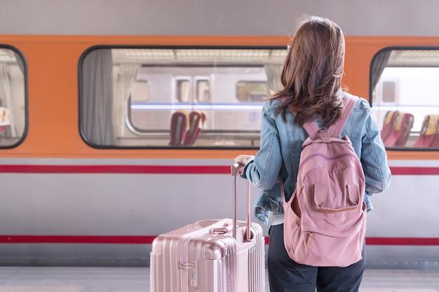 Jovem viajante com bolsa rosa e bagagem esperando o trem, espaço de cópia, conceito de viagem