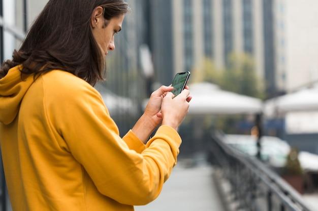 Jovem viajante com cabelo comprido, verificando seu telefone