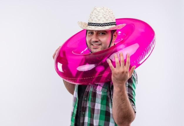 Jovem viajante com camisa xadrez e chapéu de verão com mochila e anel inflável em volta do pescoço sorrindo alegremente em pé sobre uma parede branca