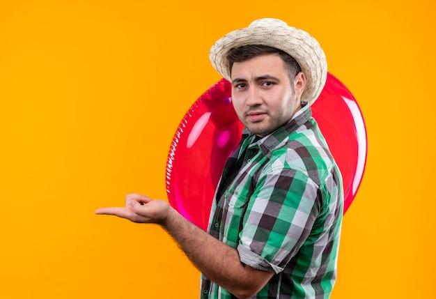 Jovem viajante com camisa xadrez e chapéu de verão segurando um anel inflável apontando com o dedo para algum lugar confuso em pé sobre a parede laranja