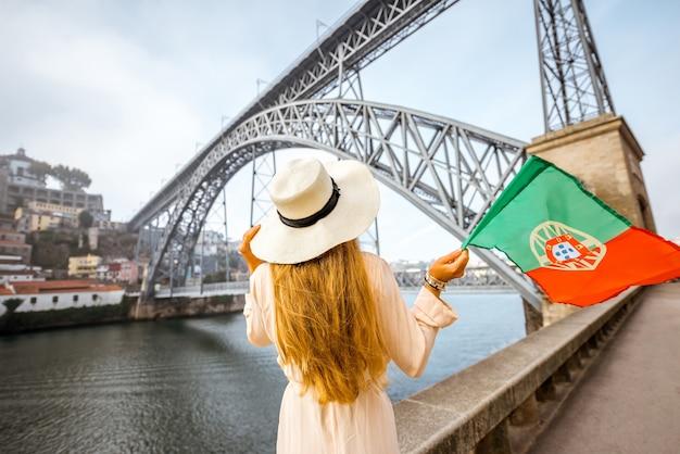Jovem viajante com chapéu de sol em pé atrás com bandeira portuguesa e a famosa ponte de ferro ao fundo na cidade do porto