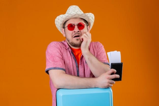 Jovem viajante com chapéu de verão usando óculos escuros segurando uma mala e passagens aéreas, olhando para a câmera estressada e nervosa em pé sobre um fundo laranja