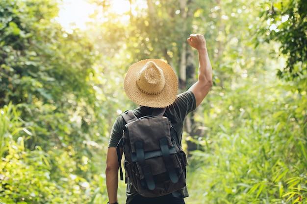Jovem viajante com chapéu e mochila em pé ao ar livre com os braços abertos.