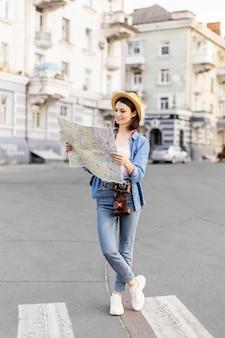Jovem viajante com chapéu, verificando o mapa