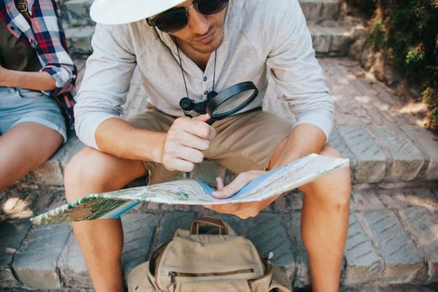 Jovem viajante com mapa e lupa