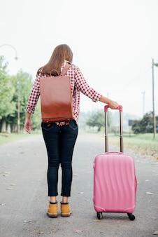 Jovem viajante com mochila e bagagem rosa