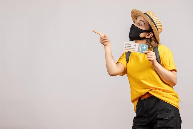Jovem viajante com mochila e máscara preta segurando um bilhete de viagem