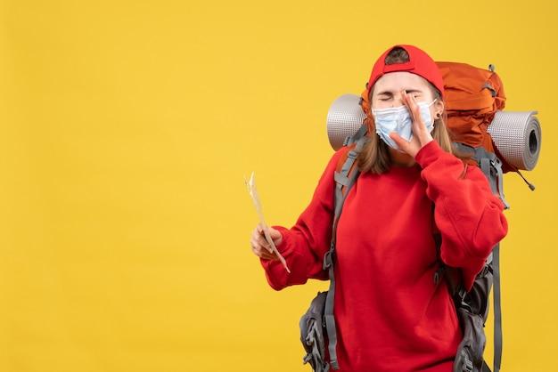 Jovem viajante com mochila e máscara segurando mapa chamando alguém de frente