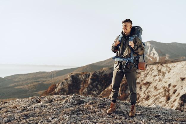 Jovem viajante com mochila grande, caminhando nas montanhas