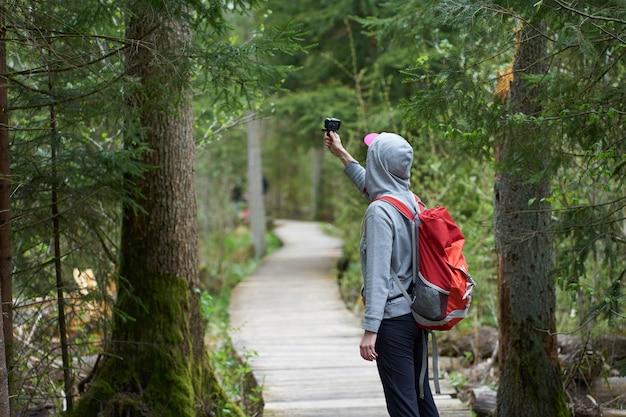 Jovem viajante com mochila laranja andando na ponte na reserva natural e filmar vídeo com uma câmera de ação.