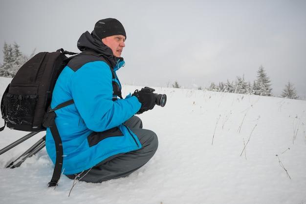 Jovem viajante com mochila tira fotos de um belo pinheiro nevado alto em um monte de neve contra o pano de fundo de neblina em um dia gelado de inverno