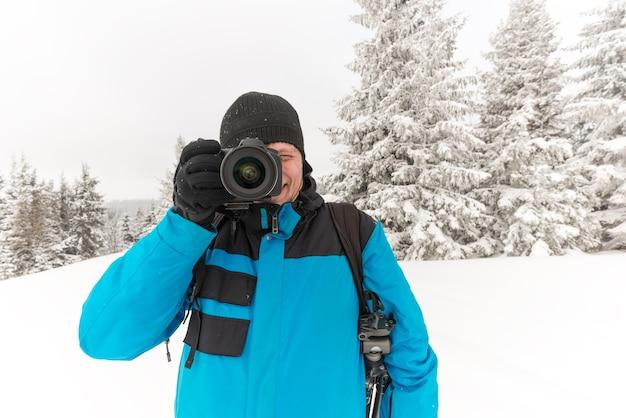Jovem viajante com mochila tira fotos de um belo pinheiro nevado alto em um monte de neve contra o pano de fundo de névoa em um dia gelado de inverno