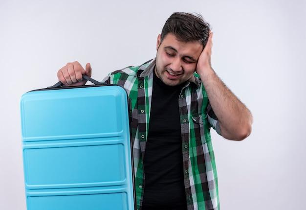 Jovem viajante com uma camisa xadrez segurando uma mala e parecendo confuso com uma mão na cabeça por engano em pé sobre uma parede branca