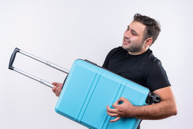 Jovem viajante com uma camiseta preta segurando uma mala e usando como um violão, sentindo-se alegre, se divertindo em pé sobre uma parede branca