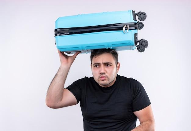 Jovem viajante com uma camiseta preta segurando uma mala na cabeça e olhando para o lado preocupado em pé sobre uma parede branca