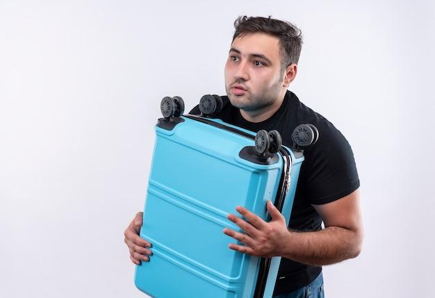 Jovem viajante com uma camiseta preta segurando uma mala, parecendo de lado confuso e preocupado em pé sobre uma parede branca