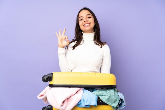 Jovem viajante com uma mala cheia de roupas isolado parede roxa mostrando sinal okey com os dedos