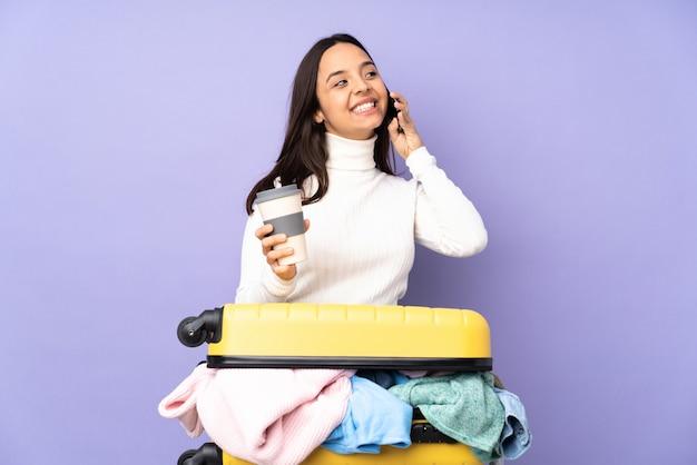 Jovem viajante com uma mala cheia de roupas isolado parede roxa segurando café para levar e um celular