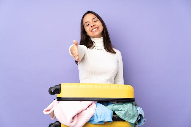 Jovem viajante com uma mala cheia de roupas sobre parede roxa isolada, apertando as mãos para fechar um bom negócio