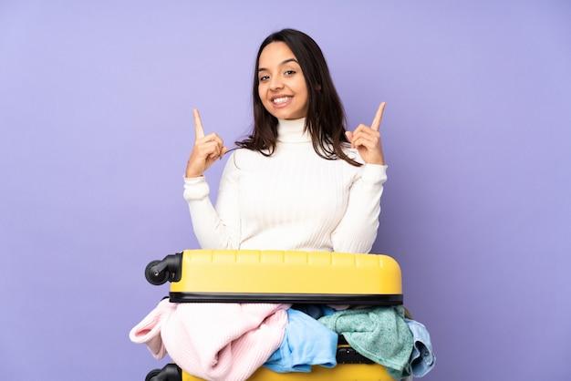 Jovem viajante com uma mala cheia de roupas sobre parede roxa isolada apontando uma ótima idéia