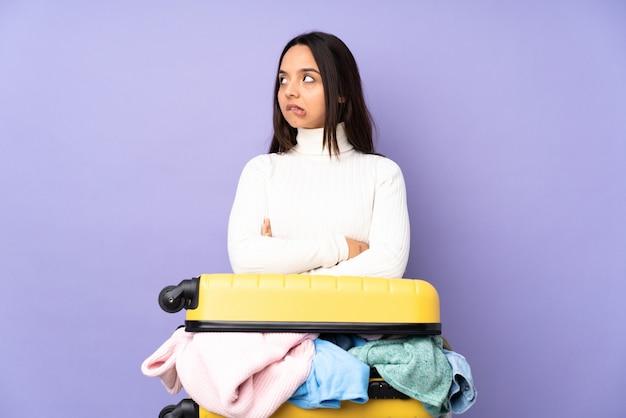 Jovem viajante com uma mala cheia de roupas sobre parede roxa isolada com confundir a expressão do rosto