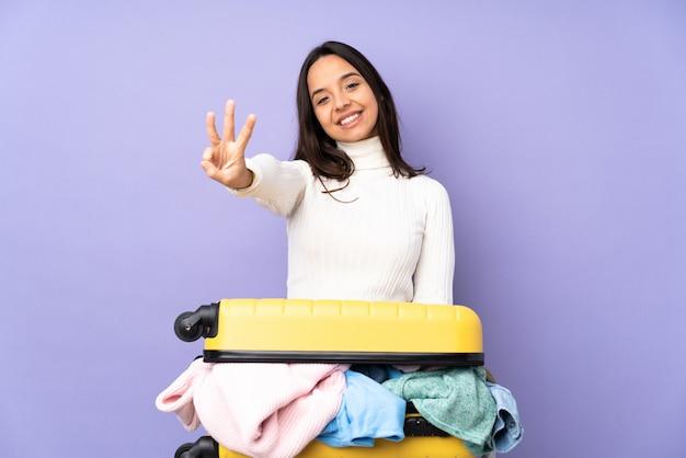 Jovem viajante com uma mala cheia de roupas sobre parede roxa isolada feliz e contando três com os dedos