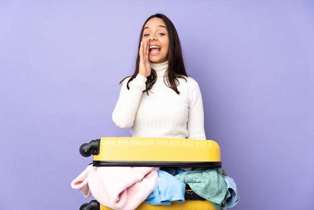 Jovem viajante com uma mala cheia de roupas sobre parede roxa isolada, gritando com a boca aberta