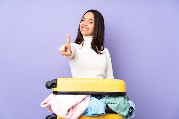 Jovem viajante com uma mala cheia de roupas sobre parede roxa isolada, mostrando e levantando um dedo
