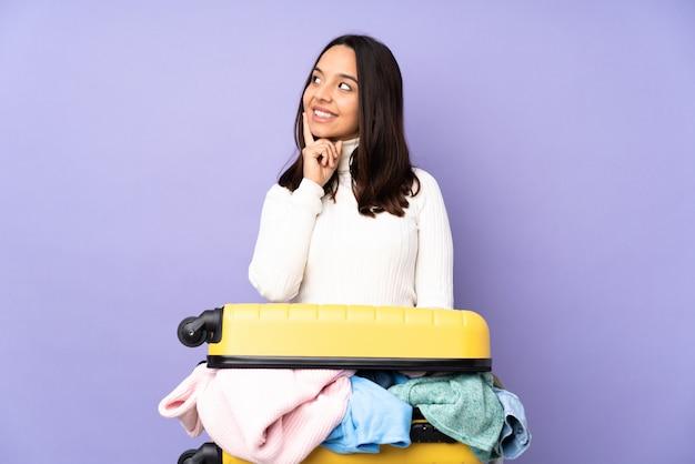 Jovem viajante com uma mala cheia de roupas sobre parede roxa isolada, pensando uma idéia enquanto olha para cima