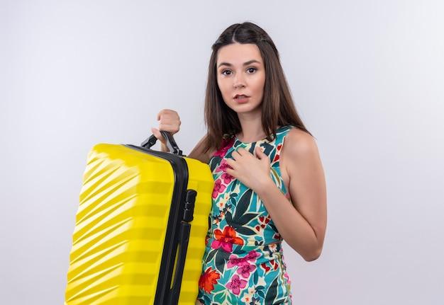 Jovem viajante confiante usando um vestido multicolorido segurando uma bolsa móvel na parede branca