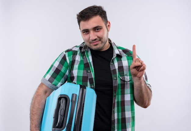 Jovem viajante de camisa xadrez segurando uma mala com um sorriso confiante no rosto mostrando o dedo indicador em pé sobre uma parede branca