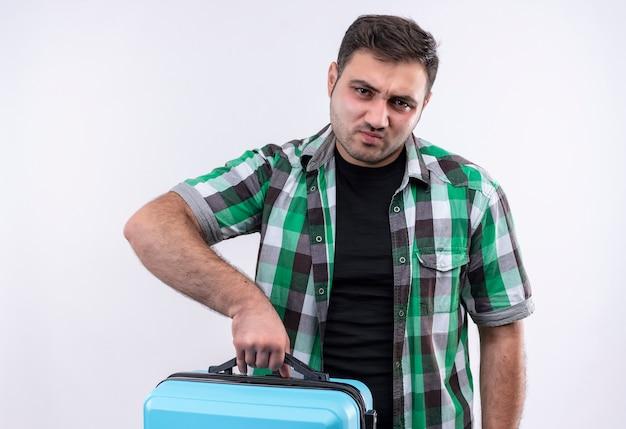 Jovem viajante de camisa xadrez segurando uma mala com uma expressão triste no rosto em pé sobre uma parede branca