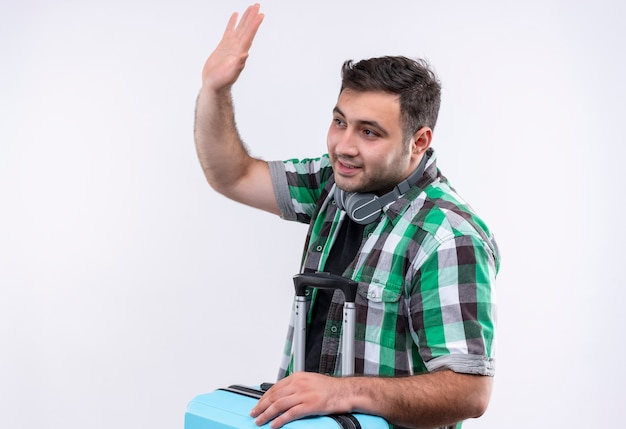 Jovem viajante de camisa xadrez segurando uma mala olhando para o lado, sorrindo, acenando com a mão em pé sobre a parede branca