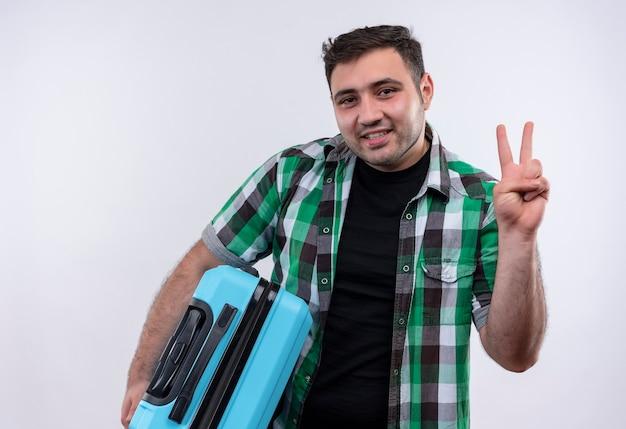 Jovem viajante de camisa xadrez segurando uma mala, sorrindo e mostrando o número três com os dedos em pé sobre uma parede branca